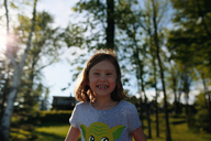 Close-up portrait of happy girl standing against trees - CAVF23061