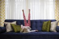 Playful girl balancing upside down on sofa at home - CAVF23106