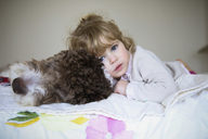 Portrait of girl relaxing with dog on bed at home - CAVF23118