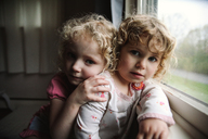 Portrait of sisters leaning on window sill at home - CAVF23151