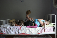 Daughters on mother with dogs lying on bed against wall at home - CAVF23172