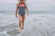 Girl playing in waves at Cape May Beach against sky - CAVF23205