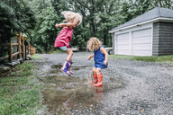 Playful sisters jumping in puddle - CAVF23217