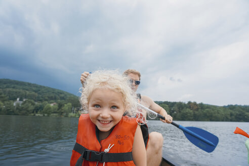 Happy daughter in canoe with father canoeing in background against stormy clouds - CAVF23223