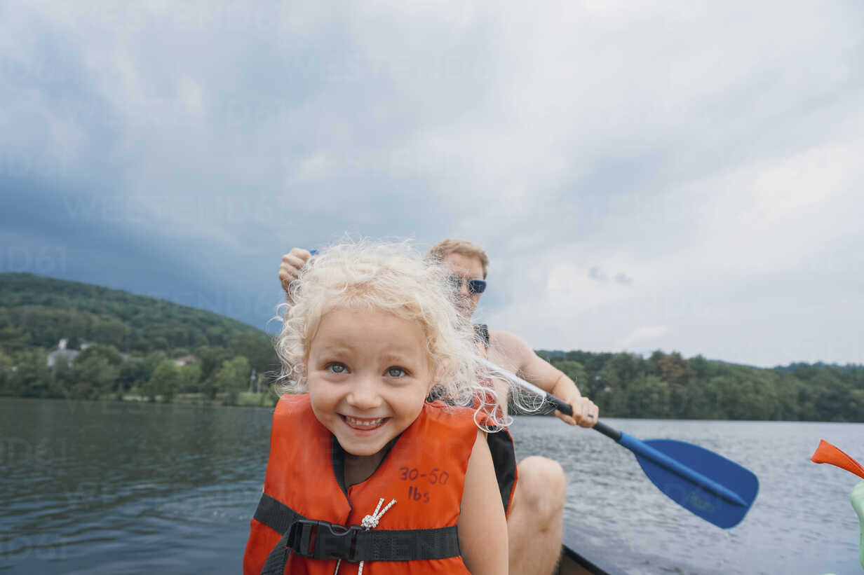 Happy daughter in canoe with father canoeing in background against stormy clouds - CAVF23223 - Cavan Images/Westend61