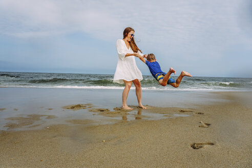 Playful mother swinging son on shore at beach against sky - CAVF23232