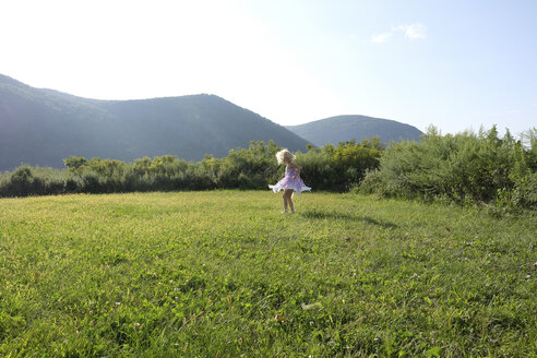 Playful girl spinning on grassy field against mountains and sky - CAVF23241