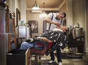 Barber shaving man's beard in shop - CAVF23253