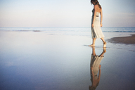 Woman walking at beach against sky - CAVF23274
