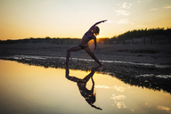 Woman wearing bikini practicing yoga at beach during sunset - CAVF23280