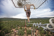 Rear view of man slacklining over forest against cloudy sky - CAVF23319