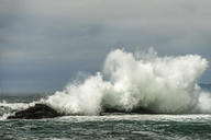 Waves splashing on rocks in sea against cloudy sky - CAVF23475