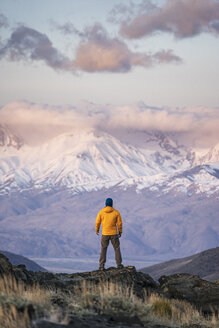 Rear view of hiker watching snowcapped mountains - CAVF23478