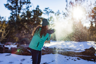 Side view of woman blowing powdered snow at field - CAVF23502