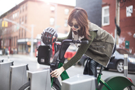 Young woman unlocking bicycle on street - CAVF23532