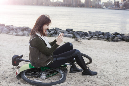 Side view of happy woman using smart phone while sitting on bicycle at beach - CAVF23535