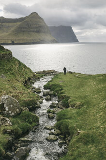High angle view of hiker standing by sea against cloudy sky - CAVF23565