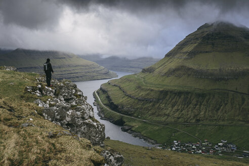 Hiker looking at view while standing on cliff against stormy clouds - CAVF23583