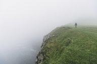 High angle view of hiker on cliff during foggy weather - CAVF23607