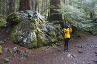 Female hiker photographing in forest - CAVF23643
