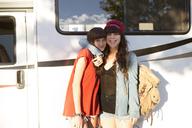 Happy young women on road trip standing together against vanity van - CAVF23676