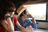 Thoughtful man sitting with woman while traveling in camper van - CAVF23679