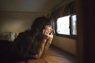 Happy woman talking on smart phone while travelling in camper van - CAVF23682