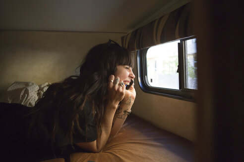 Happy woman talking on smart phone while travelling in camper van - CAVF23682