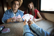 Cropped image of woman holding cards while playing with friends in camper van - CAVF23685