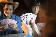 Cropped image of woman holding cards while playing with friends in camper van - CAVF23688