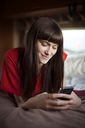 Happy woman using smart phone while relaxing on bed in camper van - CAVF23703