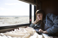 Woman looking out from window while lying on bed in camper van - CAVF23742
