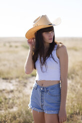 Woman wearing cowboy hat looking away while standing on field - CAVF23745