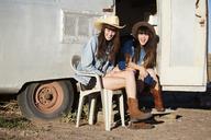 Happy friends sitting outside camper van - CAVF23751