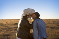 Side view of couple kissing on field against clear sky - CAVF23754