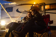 Couple sitting on chairs against camper van during night - CAVF23760