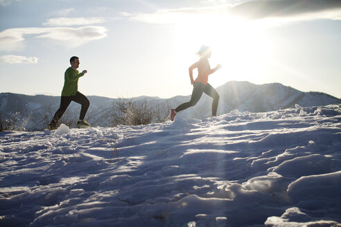 Low angle view of couple jogging on snow field against sky - CAVF23853