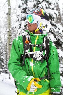 Man in ski-wear standing against tree - CAVF23856
