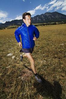 Man jogging on grass field against mountain - CAVF23883