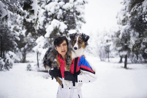 Teenage boy carrying Australian Shepherd on shoulders on snow covered field - CAVF23940