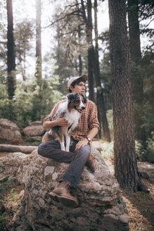 Man with Australian Shepherd sitting on rock in forest - CAVF23961