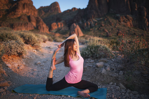 Woman practicing One-Legged King Pigeon Pose on field against mountains - CAVF23985