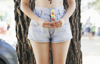 Midsection of seductive woman holding ice lolly while standing against tree trunk - CAVF24036