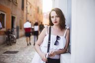 Portrait of beautiful woman leaning on wall in city - CAVF24039