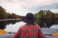 Rear view of woman kayaking in lake at forest against sky - CAVF24066