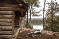 Old log cabin by lake and trees in forest - CAVF24084
