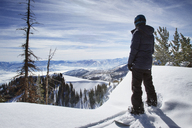 Skier standing on snow covered Wasatch Mountain against cloudy sky - CAVF24099