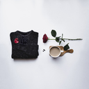 Overhead view of black sweater with coffee and rose against white background - CAVF24267