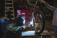 Father and son welding tricycle while working in workshop - CAVF24411