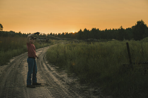 Full length of boy lassoing while standing against clear sky during sunset - CAVF24417